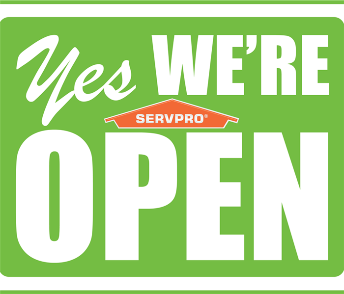 a sign that says yes we're open with a SERVPRO symbol