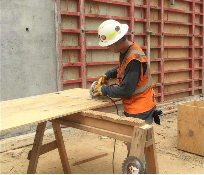 Contractor cutting wood in a commercial warehouse