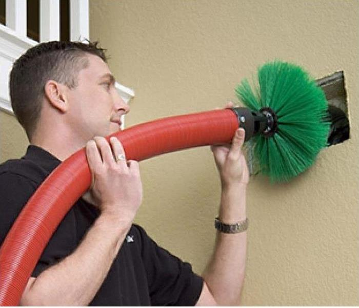 servpro employee cleaning a duct