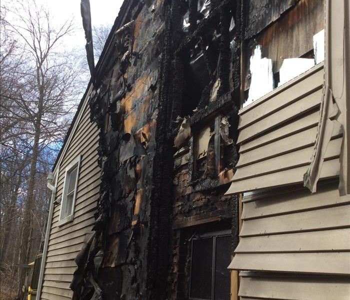 exterior of a house with vinyl siding and wood structure burned