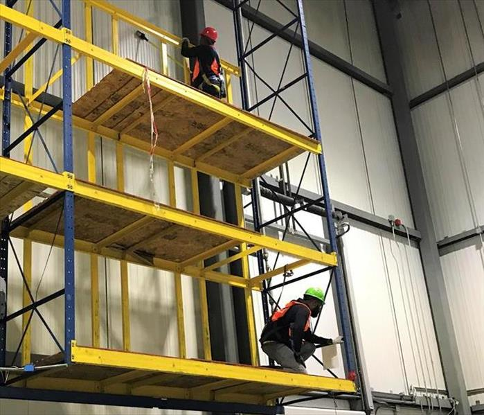 men working on top of scaffolding in a warehouse, cleaning soot off of the walls